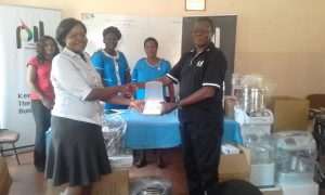 PIL General Manager handing over medical equipment to Dr. Mbewe